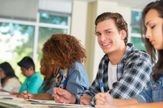 stock-photo-77616063-college-age-boy-smiling-while-taking-test-in-classroom